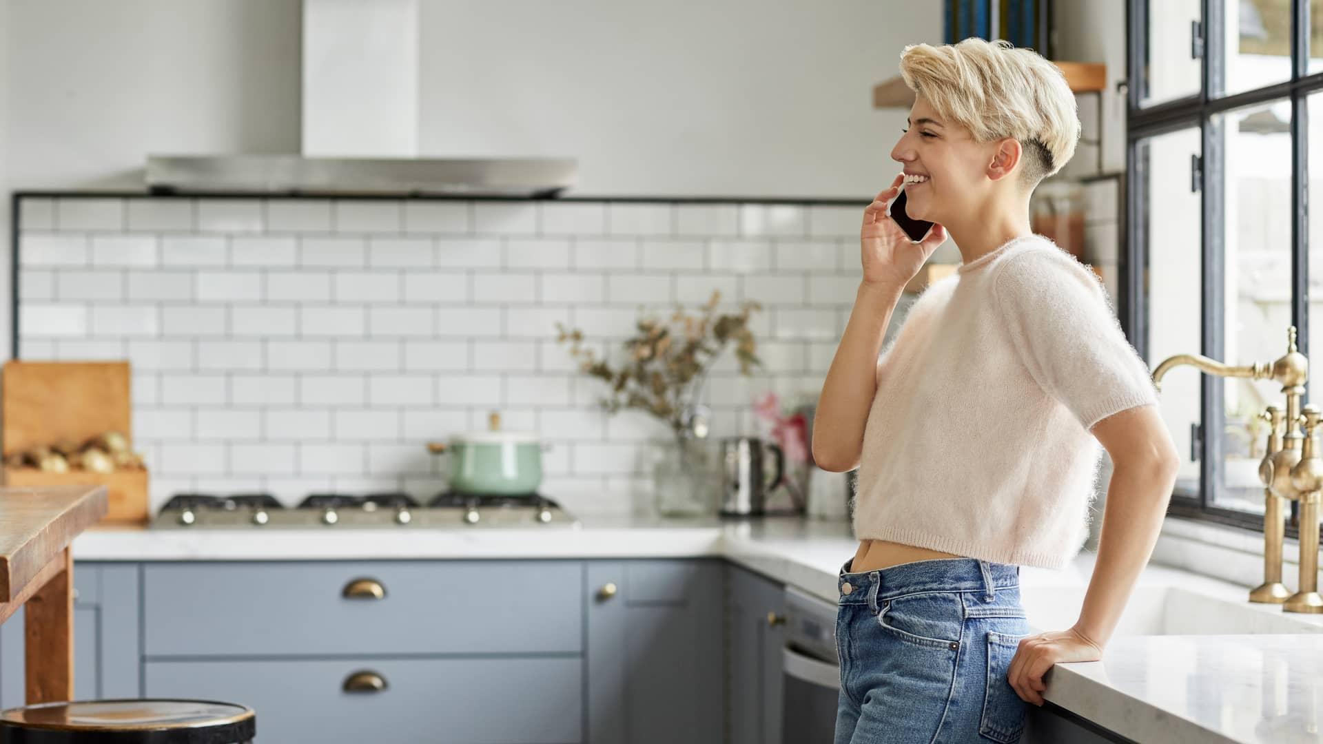 Mujer en su casa hablando por teléfono móvil simboliza teléfono fijo en el móvil