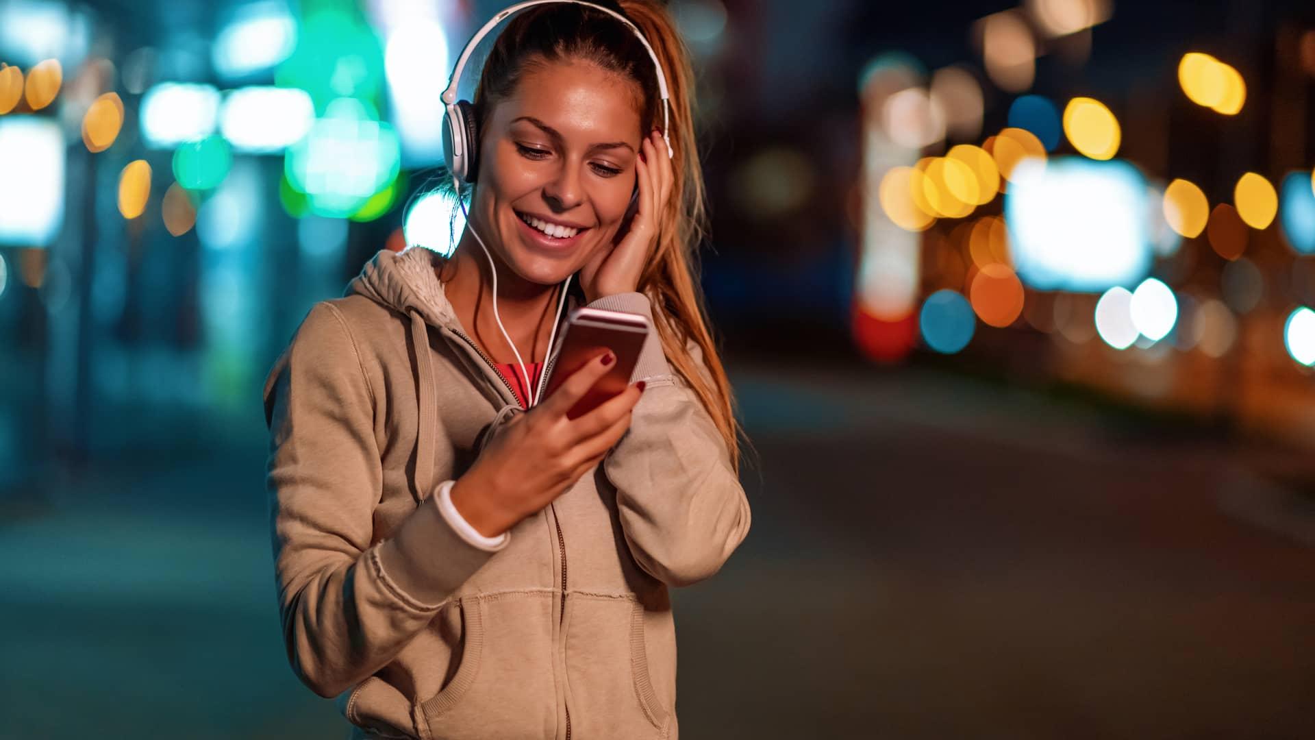 Mujer practicando deporte mientras escucha música con su teléfono gracias a la mejor tarifa