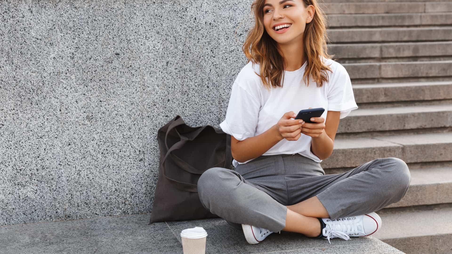Joven con su móvil mientras recarga su vehículo eléctrico simboliza recargar móvil