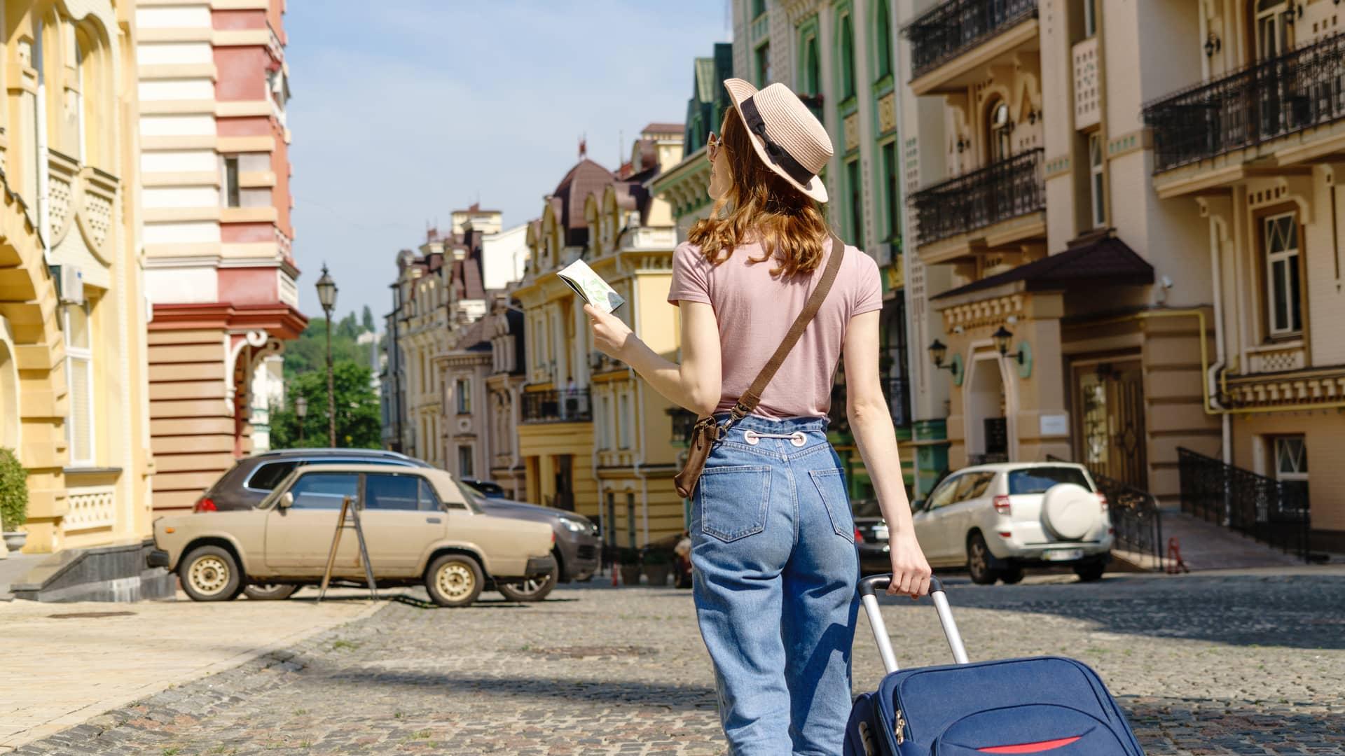Mujer joven turista con maleta y mapa simboliza roaming unión europea