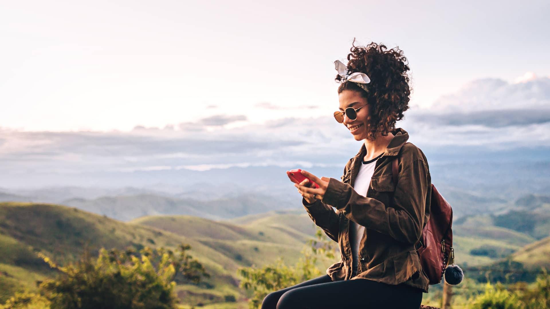 Joven leyendo un sms en su telefono móvil somboliza tarifa móvil barata