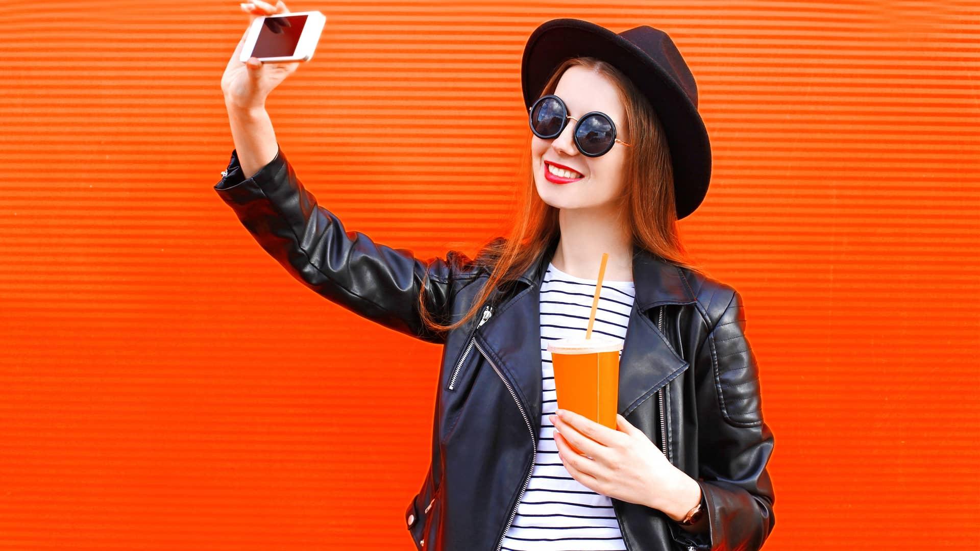 Joven haciendose un selfie con su bebida favorita simboliza móviles euskaltel