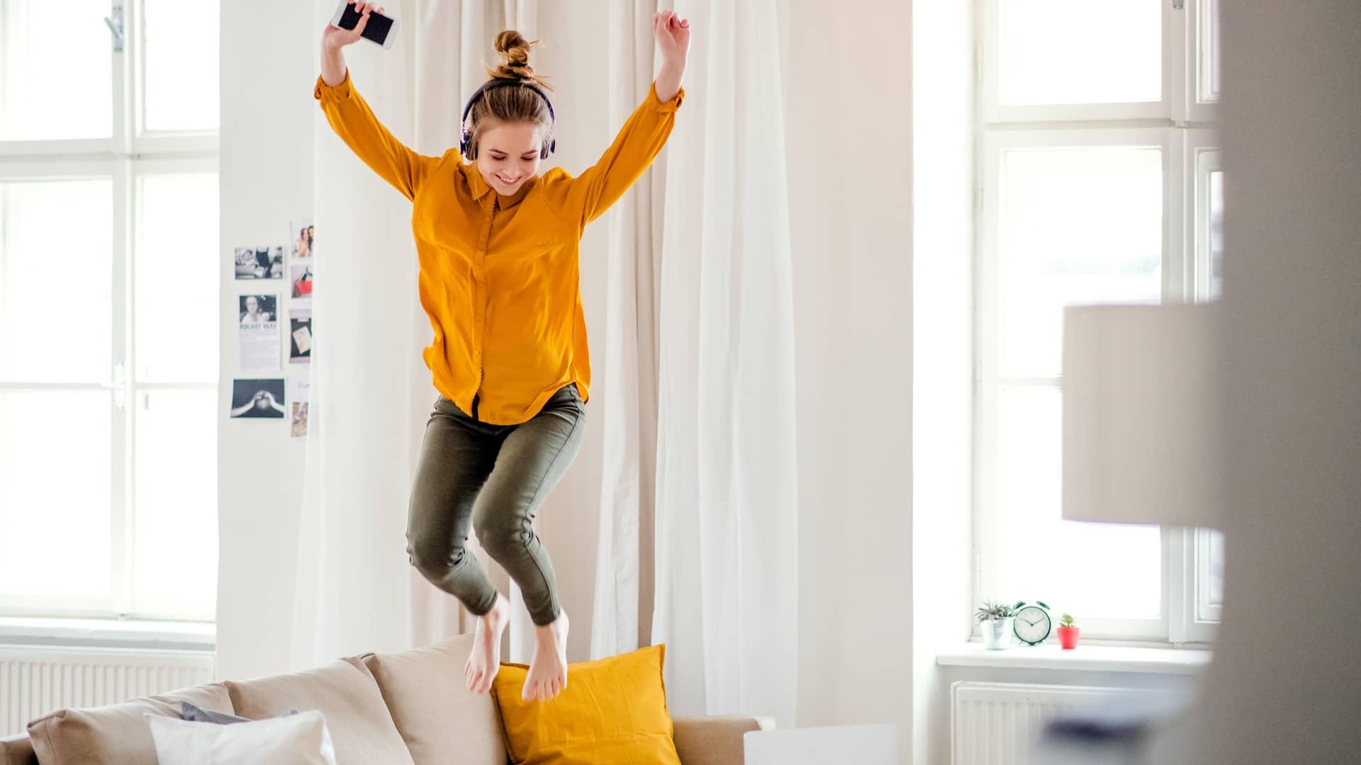 Una joven estudiante con auriculares saltando en el sofá simboliza portabilidad másmovil