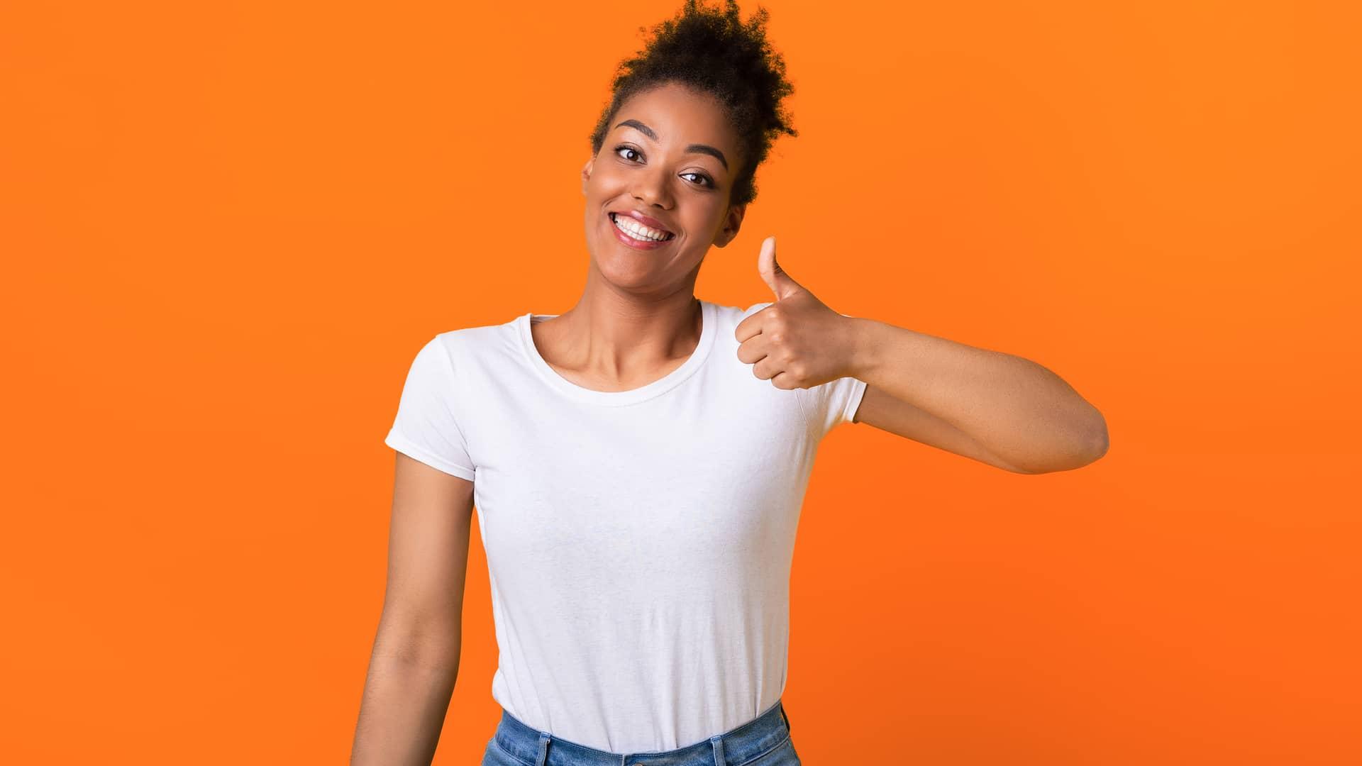 Mujer mostrando pulgar hacia arriba y sonriendo simboliza opinión clientes simyo