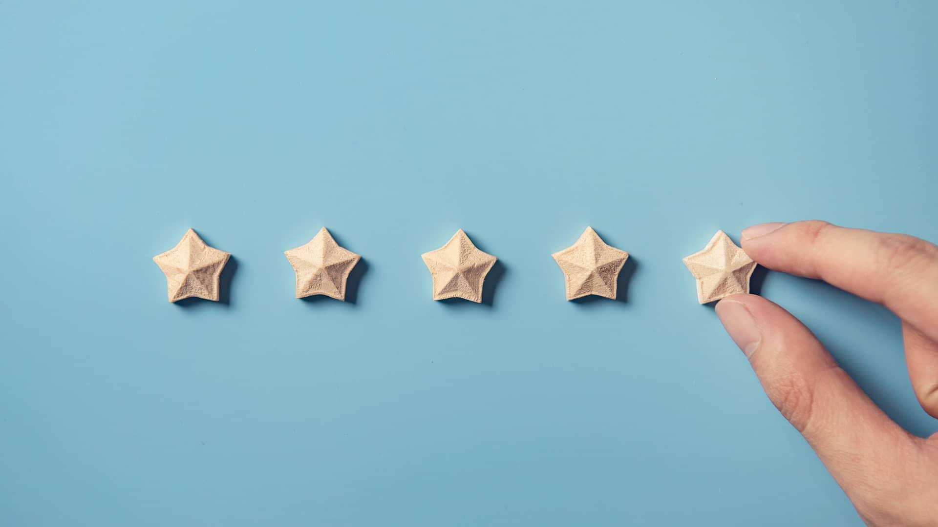 Persona colocando cinco estrellas representa la opinión sobre compañía suop
