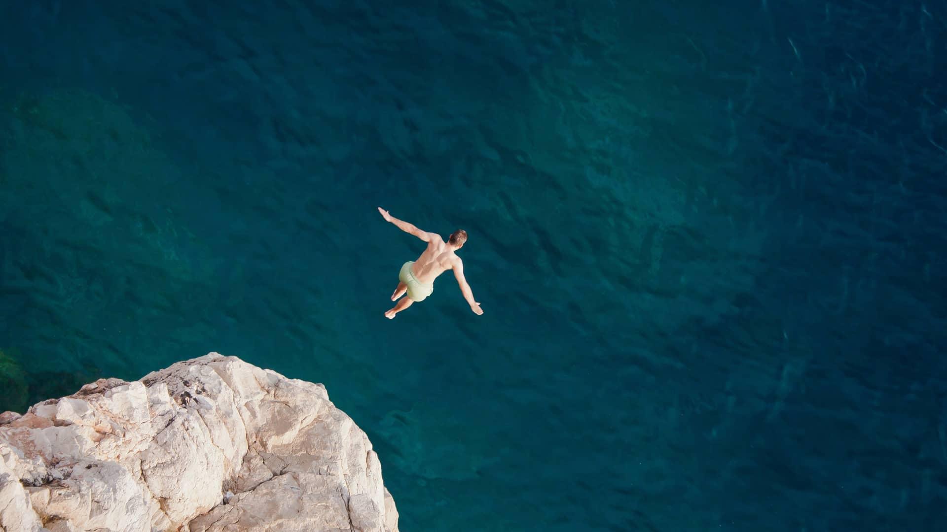 Joven saltando hacia el mar simboliza portabilidad compañía suop