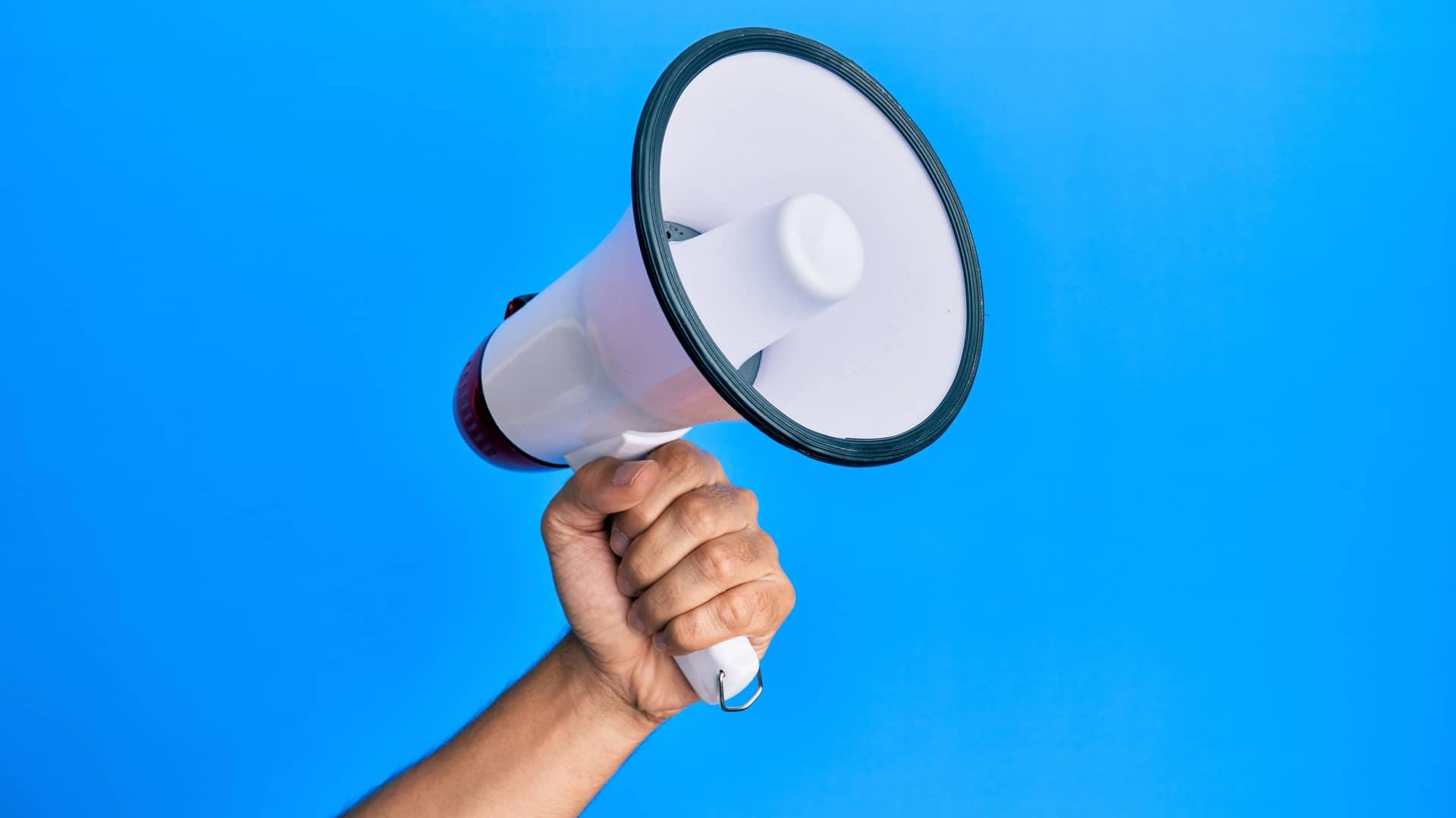 Mano de joven con megáfono simboliza opinión sobre telecable