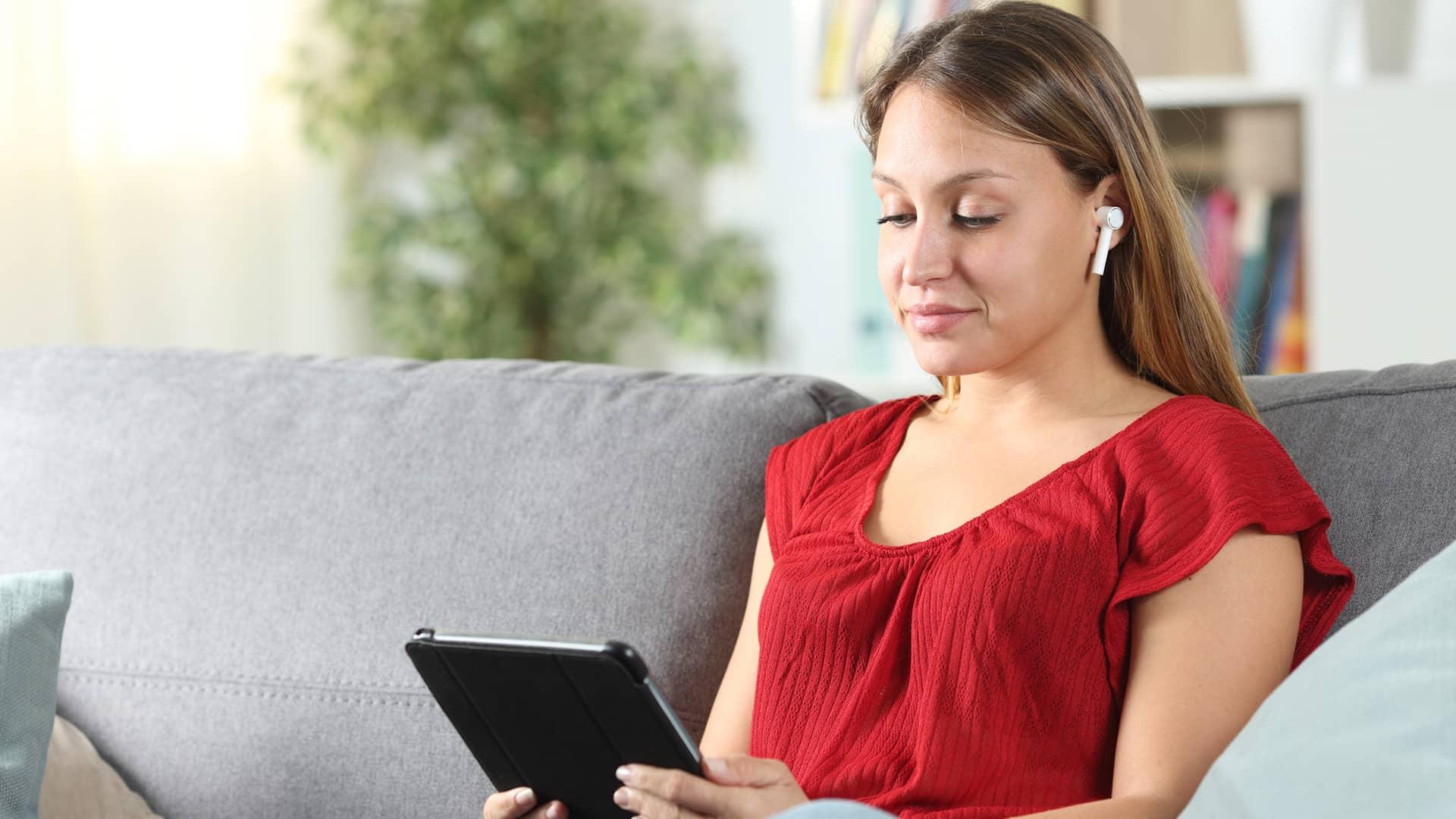 Joven viendo serie en tablet con móvil internet tv vodafone