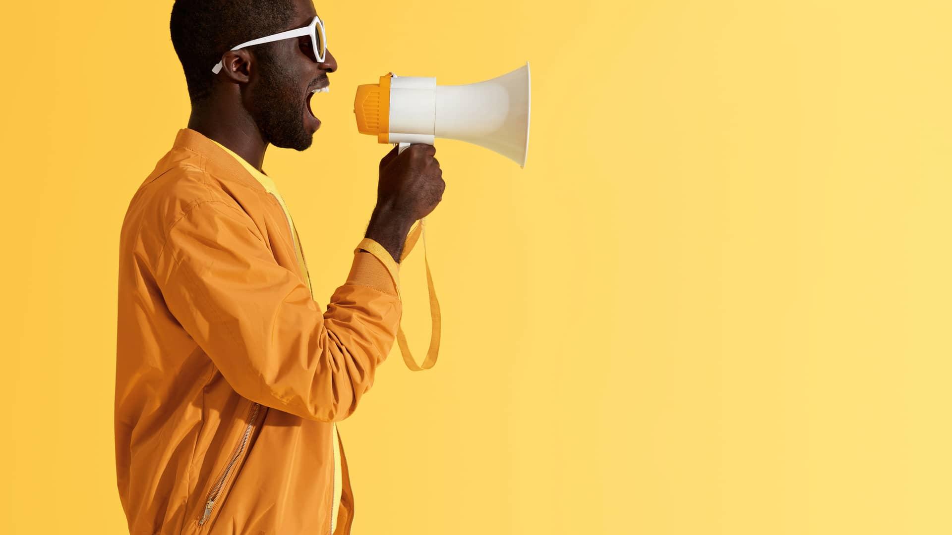 Joven con megáfono representa opinión de clientes yoigo