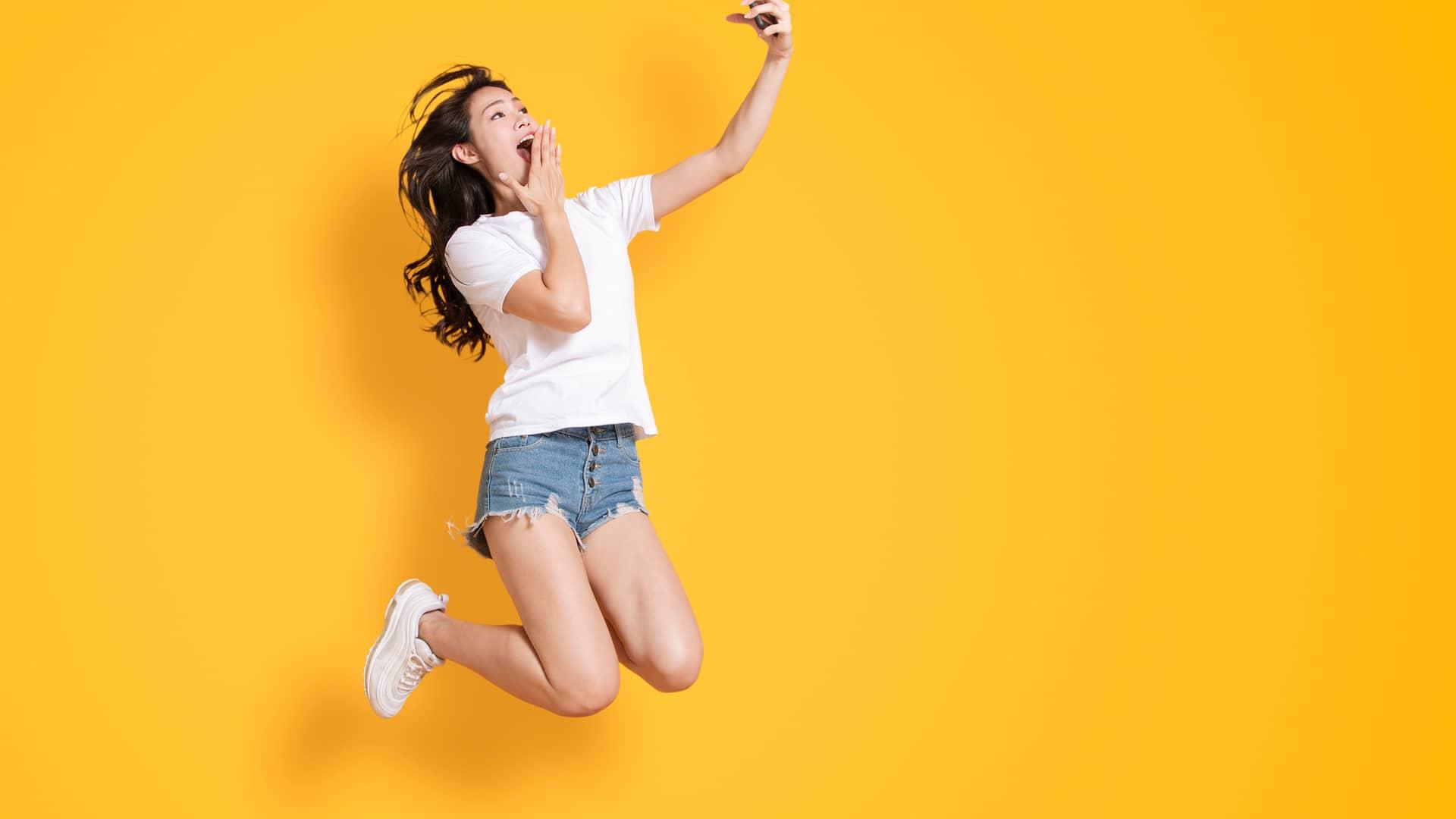 Joven saltando con smartphone representa portabilidad de yoigo