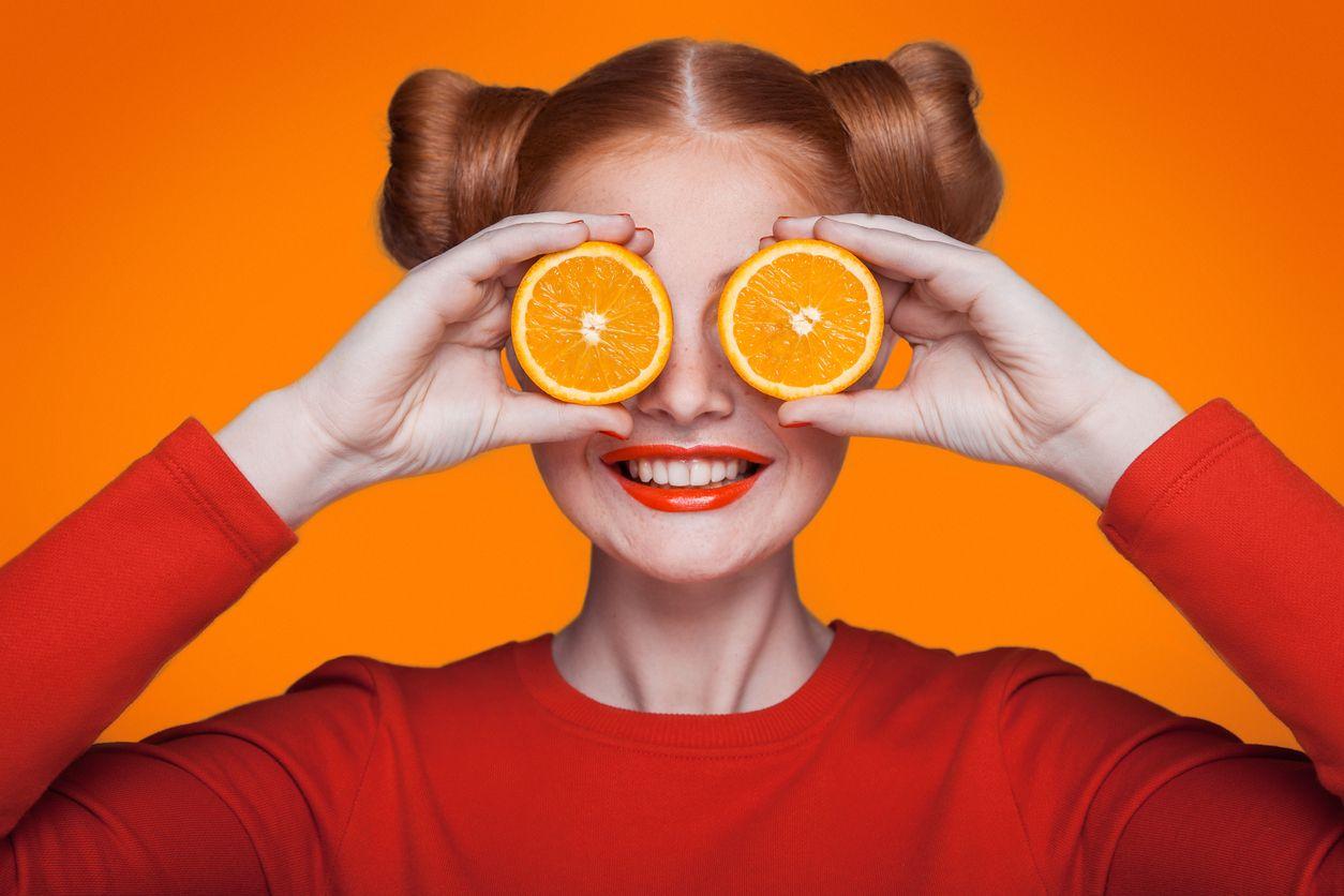Chica se tapa con dos naranjas feliz por el descuento ser de orange