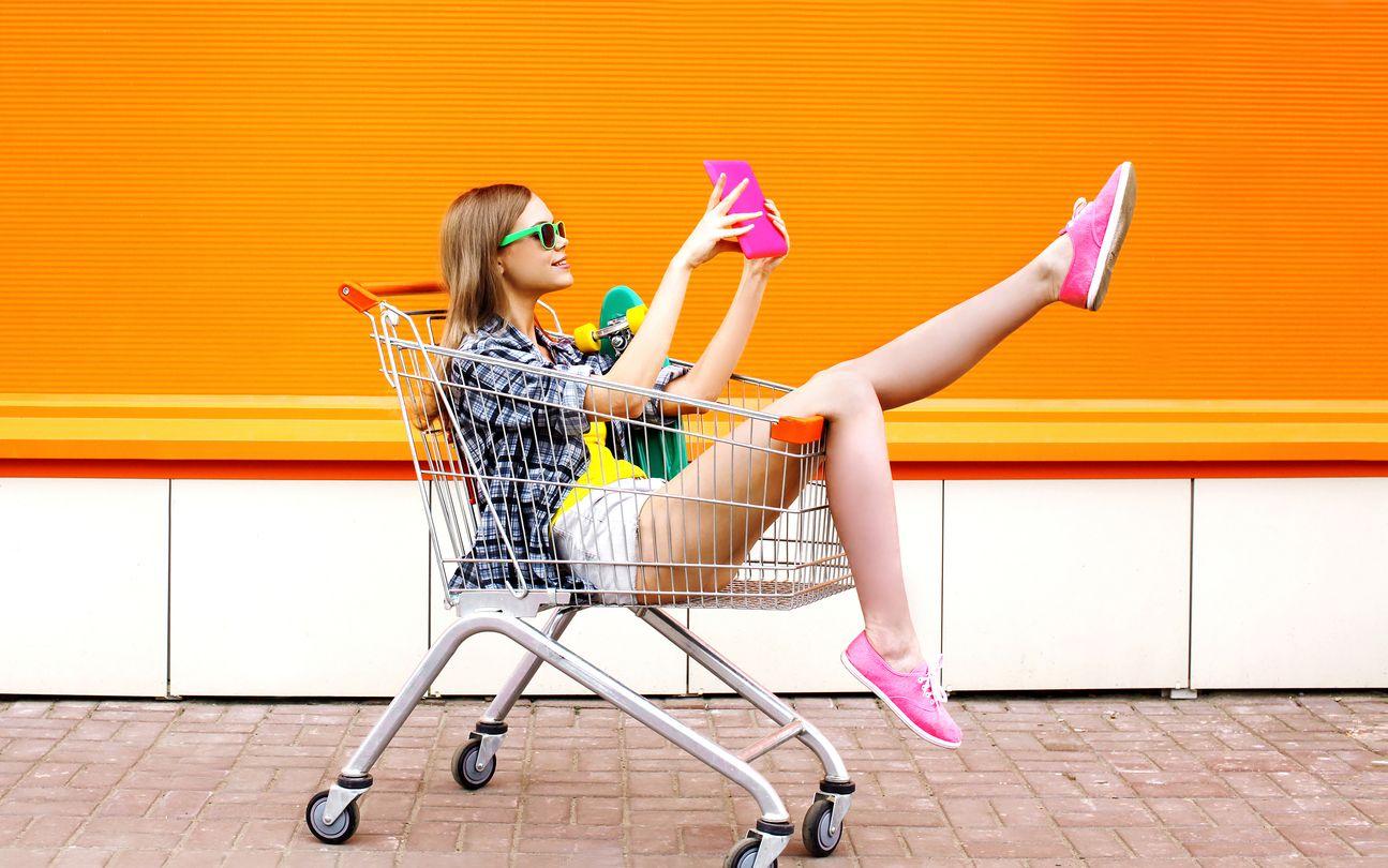 Chica en un carro de la compra disfrutando de Orange recarga y gana