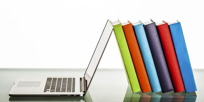 Ordenador con la fibra low cost, sujetando libros