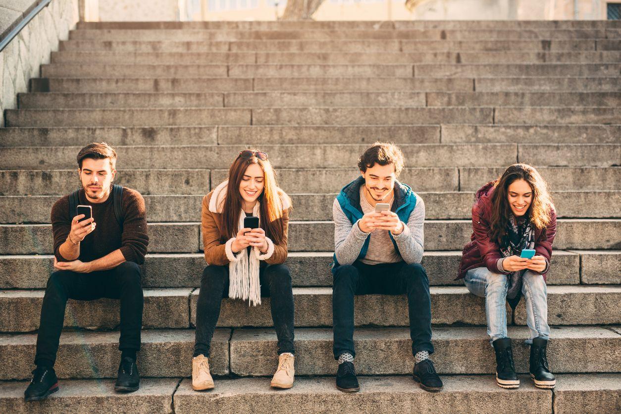 Jóvenes con el móvil y el Internet 4G con cobertura Orange