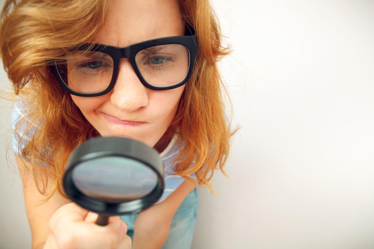 Chica busca con lupa la letra pequeña de tarifas
