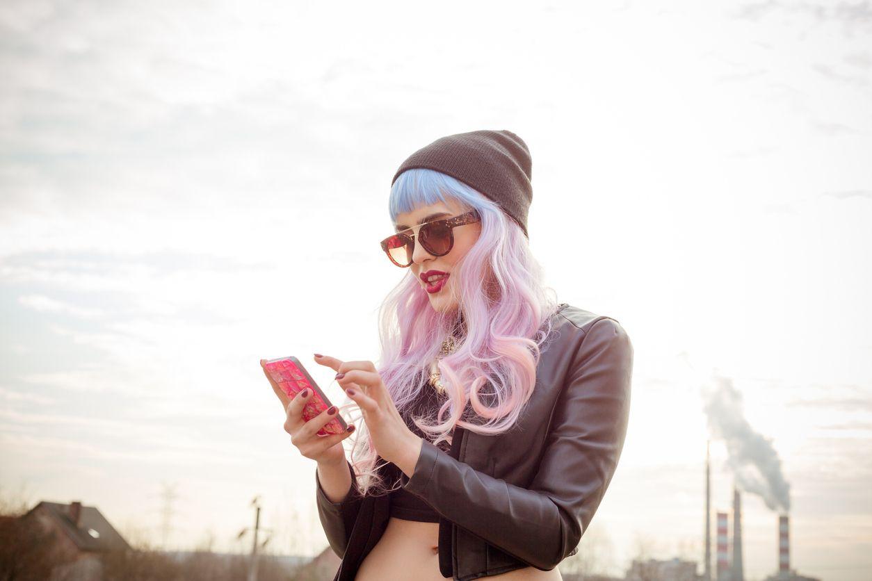 Chica con el pelo de colores disfrutando del móvil con Tuenti prepago
