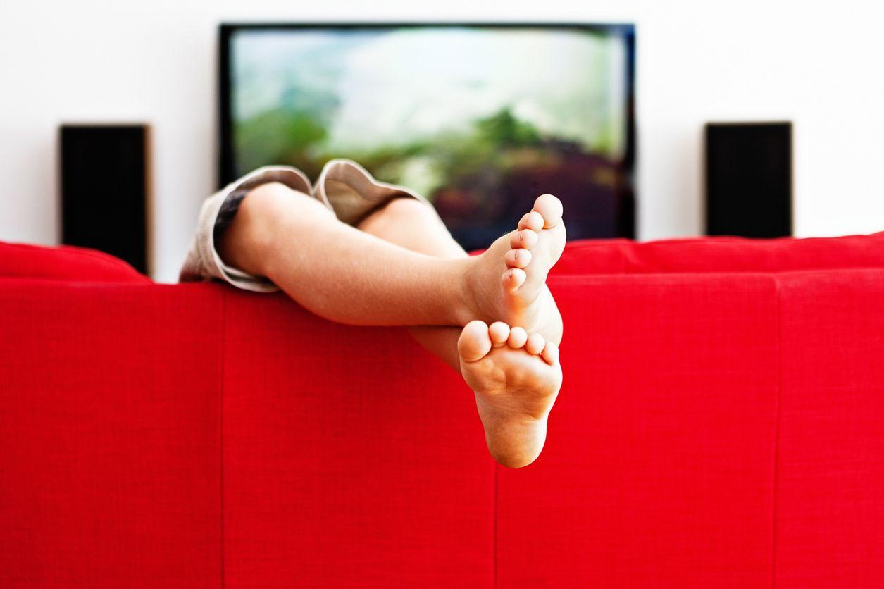 Pies de una chica viendo los canales vodafone 4k