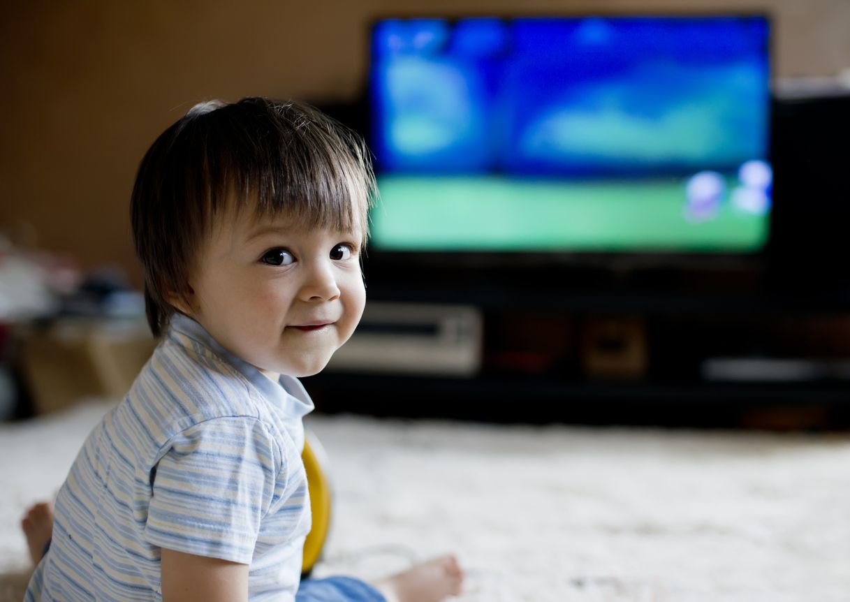 Niño ve en la televisión canales infantiles