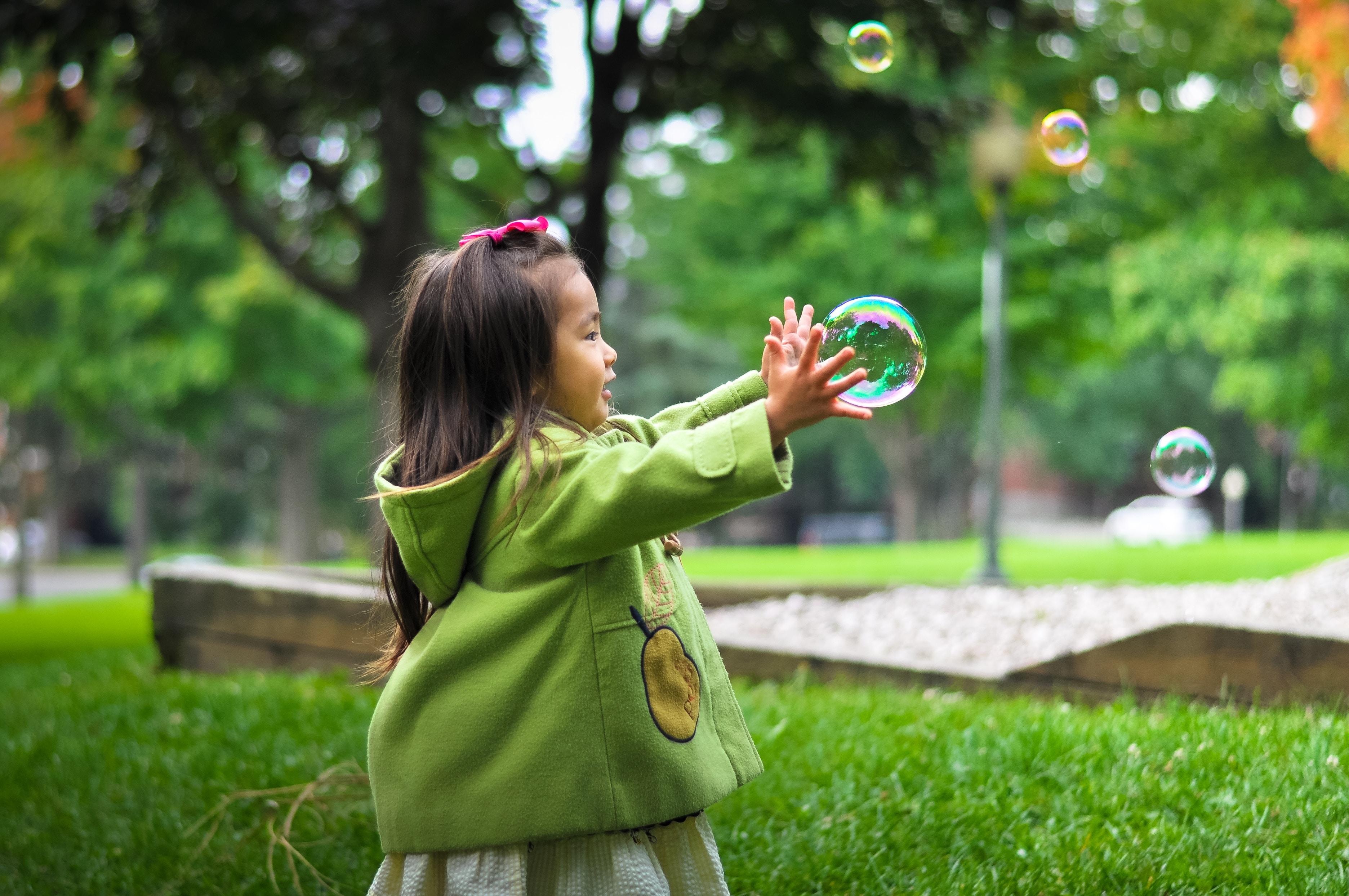 Niña juega con pompas y el brazalete gps para niños yoigo